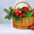 Christmas decorations in basket and spruce branches on table on bright background — Stock Photo #48028123