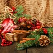 Christmas decorations in basket and spruce branches on table on brown background — Stock Photo #48028133