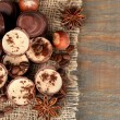 Tasty chocolate candies with coffee beans and nuts on wooden background — Stock Photo #48028575