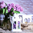 Beautiful lilac flowers in vase, on color wooden  background — Stock Photo #48028851