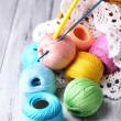 Colorful clews, napkin and crochet hook in wicker basket, on wooden background — Stock Photo #48029231