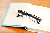 Composition with old book, eye glasses,  on wooden background — Stock Photo