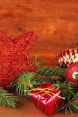 Beautiful Christmas decorations on fir tree on table on wooden background — Zdjęcie stockowe