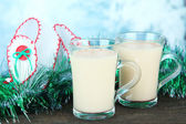 Cups of eggnog with tinsel and Christmas shoes on table on bright background — Stock Photo