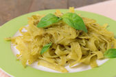 Delicious pasta with pesto on plate on table close-up — Zdjęcie stockowe