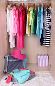 Female clothes in wardrobe and suitcase in room — Stock Photo