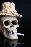 Skull in wicker hat with cigarette isolated on black — ストック写真