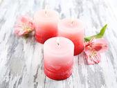 Hermosas velas con flores sobre fondo de madera — Foto de Stock