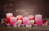 Hermosas velas con flores en la mesa sobre fondo marrón — Foto de Stock
