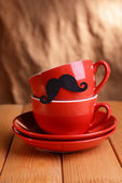 Cup with mustache on table on brown background — Foto de Stock