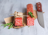 Tasty salami sausage, on paper on wooden background — Stock Photo