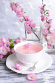 Beautiful fruit blossom with cup of tea on table on grey background — Foto de Stock