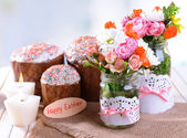Beautiful bouquet of bright flowers in jars on table on light background — Stock fotografie