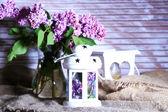 Hermosas lilas flores en florero, sobre fondo de madera de color — Foto de Stock