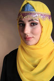 Beautiful muslim arabic woman on dark color background — Stockfoto