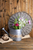 Bright wildflowers in watering can on wooden background — Stock Photo