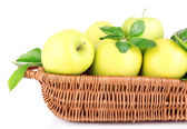 Ripe sweet apples with leaves in wicker basket, isolated on white — Stock Photo