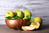 Ripe sweet apples with leaves in bowl on wooden background — Foto de Stock