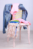 Clothes on chair on gray background — Stock fotografie