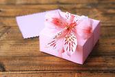 Rosa gåva med båge och blomma på träbord närbild — Stockfoto