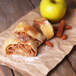 Tasty homemade apple strudel on paper napkin, on wooden background — Stock Photo #48031143