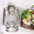 Beautiful flowers in crate with kerosene lamp on wooden stand on light background — Stock Photo #48034515