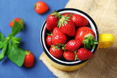 Ripe sweet strawberries in mug  on color wooden background — Stock Photo