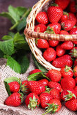 Ripe sweet strawberries in wicker basket and mint leaves on wooden background — Stock fotografie