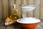 Sifting flour into bowl on table on wooden background — Stock fotografie