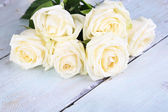 Beautiful white roses on wooden table — Stock Photo