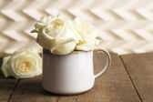 Beautiful white roses in cup on wooden table — Stock Photo