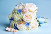 Beautiful wedding bouquet with roses on blue background — Stock Photo