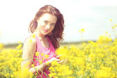 Beautiful young woman with cherries in field — Stock Photo
