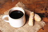 Cup with hot coffee on sackcloth napkin, on wooden table background — Foto de Stock