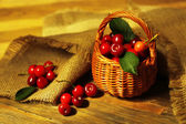 Sweet cherries in wicker basket on wooden table  — Stock fotografie