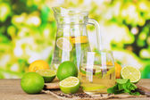 Fresh summer drink with lime and cloves in glass and jug, on color wooden table, on bright background — Stock Photo