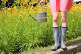Young woman in rubber boots holding watering can, outdoors — Stock Photo