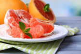 Ripe peeled grapefruits on plate, on color wooden table, on light background — Stock Photo
