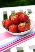 Ripe sweet strawberries in bowl on table in garden — Foto de Stock