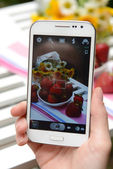 Hand making photo of strawberries on mobile phone for social network — Stock Photo