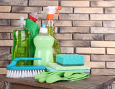 Cleaning products on shelf on bricks wall background — Stock Photo