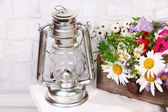 Beautiful flowers in crate with kerosene lamp on wooden stand on light background — Stock Photo