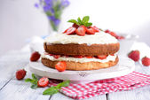 Delicious biscuit cake with strawberries on table on light background — Stock Photo