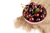 Sweet cherries in color bowl isolated on white — Stock Photo