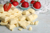White chocolate bar with fresh strawberries, on color wooden background — Foto de Stock