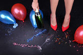 Legs with confetti, champagne and balloons on the floor — Стоковое фото
