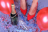 Legs with confetti, champagne and balloons on the floor — Stock fotografie