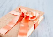 Book wrapped with color ribbon, on color wooden  background — Stock Photo