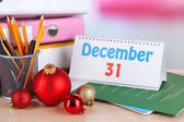 Table with office supplies, calendar and Christmas tinsel close-up — Foto Stock