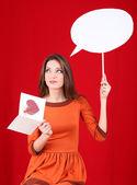 Donna attraente con cartolina, su sfondo rosso — Foto Stock